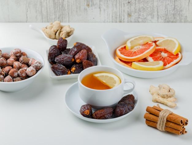 Tè allo zenzero, bastoncini di cannella, agrumi, datteri, noci in una tazza