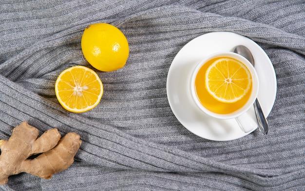 Tè allo zenzero con limone su uno sfondo a maglia grigio caldo. una bevanda fredda invernale calda e calda. vista dall'alto. disteso.