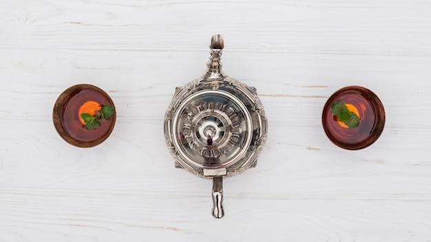 Tè arabo in tazze con teiera sul tavolo