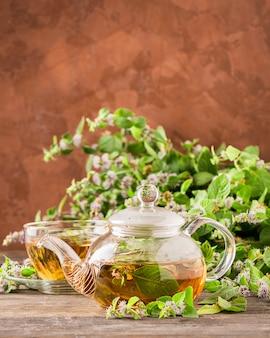 Tè aromatico fresco con la teiera di vetro delle foglie di menta della melissa su legno