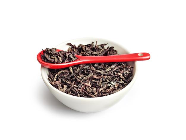 Tè asciutto della foglia in una ciotola con il cucchiaio ceramico rosso isolato su bianco