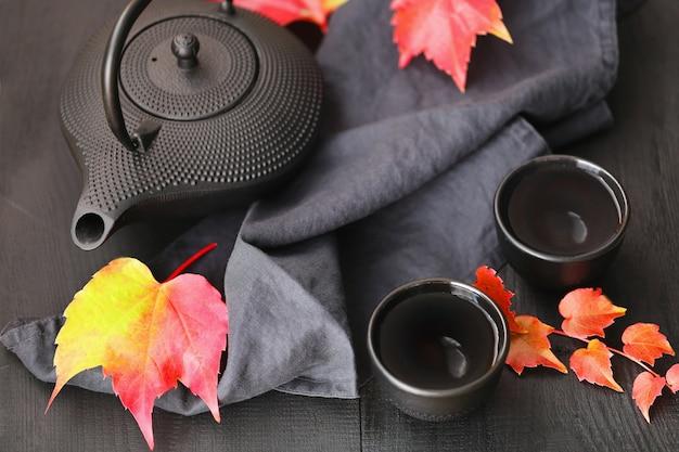 Tè autunnale in stile minimalista. teiera nera e foglie di autunno
