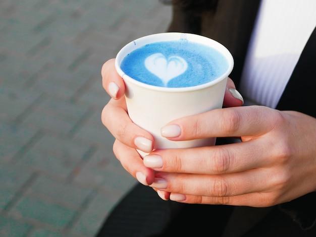 Tè blu matcha nelle mani. tè blu matcha. vista laterale del tè blu matcha. bevi sul posto. con un motivo a forma di cuore. amore per la partita. latte matcha. arte blu latte