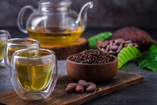Tè caldo al cacao. tisana fresca al cioccolato caldo a base di scaglie di semi di cacao, ricca di flavonoidi e antiossidanti, servita in bicchieri, messa a fuoco selettiva