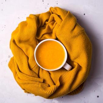 Tè caldo alla frutta all'olivello spinoso con un caldo maglione lavorato a maglia. stagione autunnale