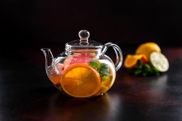 Tè caldo alla frutta con limone, menta, arancia, lime e pompelmo in una bella teiera di vetro