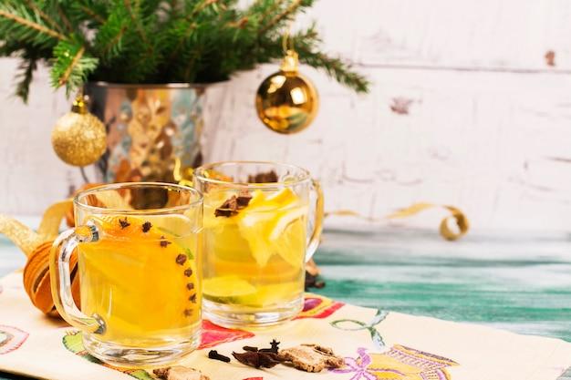 Tè caldo arancione con spezie in tazze di vetro sul tavolo di legno.