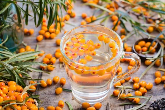 Tè caldo con bacche di olivello spinoso in un bicchiere su un tavolo di legno