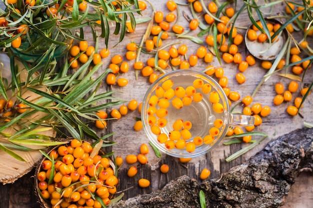 Tè caldo con bacche di olivello spinoso in un bicchiere, vista dall'alto