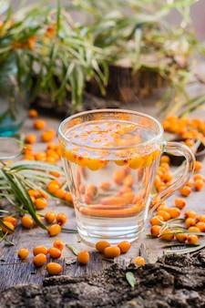 Tè caldo con bacche di olivello spinoso in un bicchiere