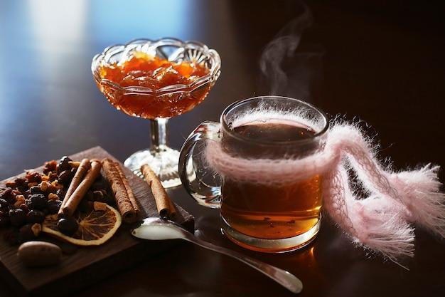 Tè caldo con marmellata su un tavolo scuro. condimenti alla cannella, chiodi di garofano, limone essiccato
