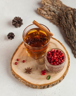 Tè caldo con spezie, mela e frutti di bosco in una tazza di vetro trasparente su un supporto in legno. il concetto di comfort domestico, autunno