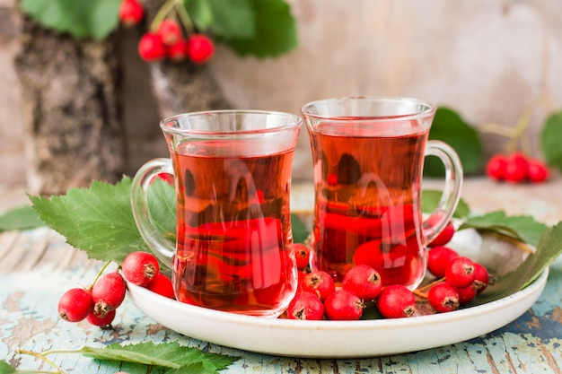 Tè caldo da bacche di biancospino in bicchieri trasparenti su un tavolo di legno