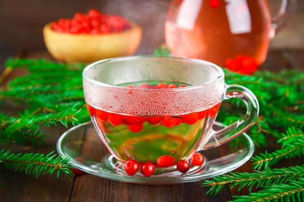 Tè caldo dai mirtilli in una tazza di vetro circondata dai rami dell'abete su una tavola di legno.