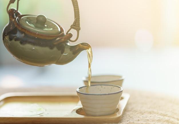 Tè caldo dalla pentola alla tazza di tè di vetro.