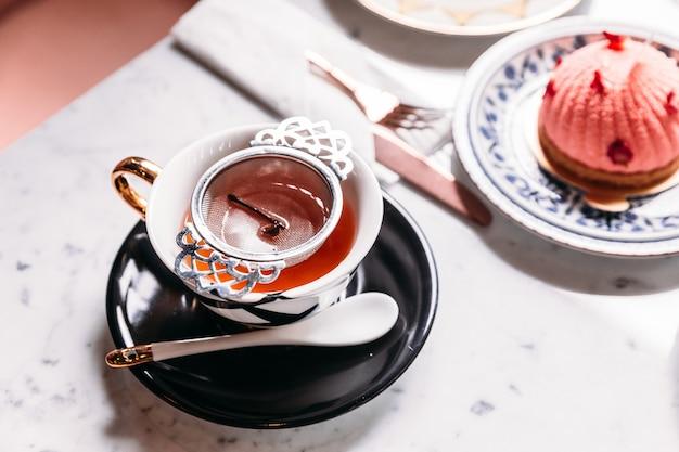 Tè caldo di mela filtrato servito in tazza vintage in porcellana con torta alle mousse sul tavolo di marmo.
