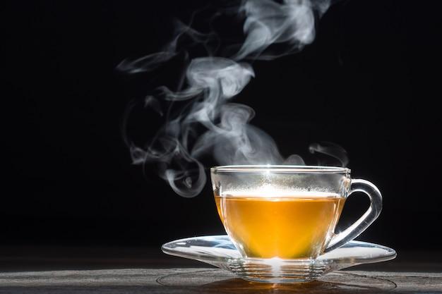 Tè caldo in teiera e tazza di vetro con vapore su fondo di legno