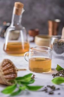 Tè caldo in teiera e tazza di vetro con vapore su sfondo scuro.