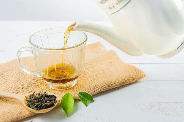 Tè con bicchiere di tè su legno bianco