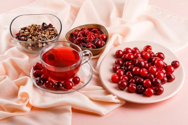 Tè con ciliegie, marmellata, erbe secche in una tazza di vetro su rosa e tessuto alto.