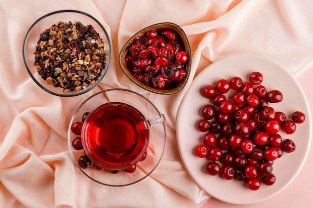 Tè con ciliegie, marmellata, erbe secche in una tazza di vetro su rosa e tessuto.