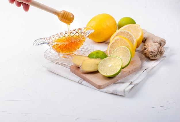 Tè con erbe, limone e zenzero su sfondo bianco e miele