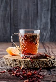 Tè con frutta secca e fiori, limone su legno in una tazza su piastrelle di pietra e superficie in legno
