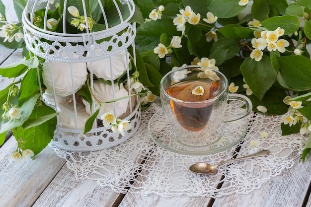 Tè con gelsomino e marshmallow in una gabbia decorativa bianca su un tavolo di legno bianco