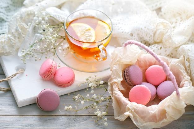Tè con limone, fiori selvatici e macaron sul tavolo di legno bianco.