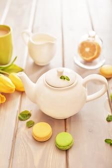 Tè con menta e limone sul tavolo con amaretti e tulipani gialli