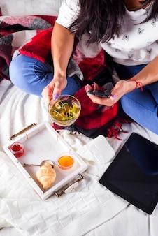 Tè con miele e marmellata su un vassoio e una ragazza con un tablet su un letto con una coperta