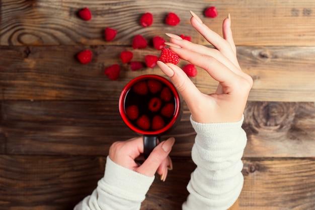 Tè curativo con lamponi e frutti di bosco sul tavolo. una tazza nelle mani di una ragazza. lotta contro il raffreddore in inverno con metodi naturali.