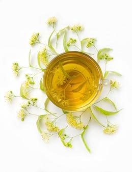 Tè dai fiori di tiglio su uno sfondo bianco.