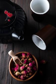 Tè dei germogli di rosa sulla ciotola di legno con la teiera