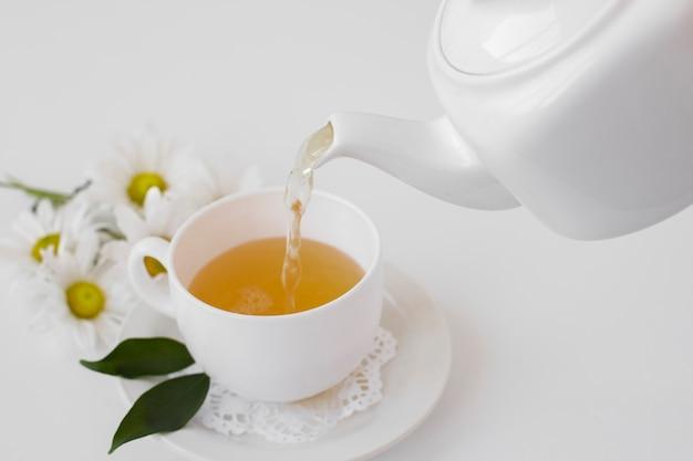 Tè del primo piano che versa nella tazza su un vassoio