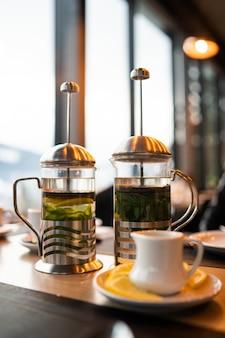 Tè dell'olivello spinoso in stampa francese con la tazza scura isolata su marmo luminoso