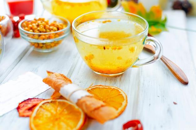 Tè dell'olivello spinoso in tazza di vetro e pastiglia di teiera e frutta