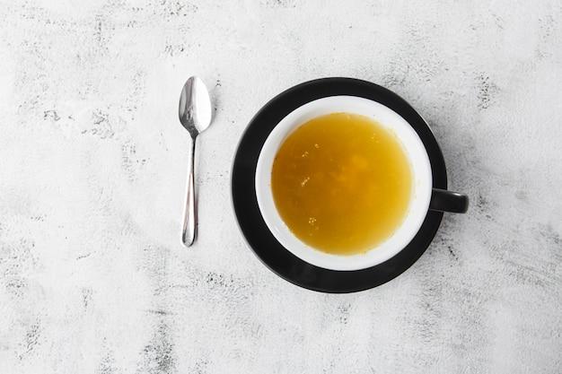 Tè dell'olivello spinoso in tazza scura isolata su fondo di marmo luminoso. vista dall'alto, copia spazio. pubblicità per menu bar. menu della caffetteria. foto orizzontale.