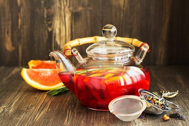 Tè di frutta e bacche in una pentola di vetro