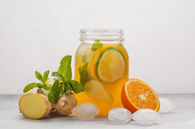 Tè di ghiaccio arancio dello zenzero con la menta in un barattolo di vetro, fondo bianco, spazio della copia. estate rinfrescante concetto di bevanda.