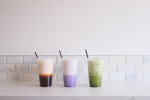 Tè di ghiaccio tailandese con il tè del latte di taro e il tè verde di matcha.