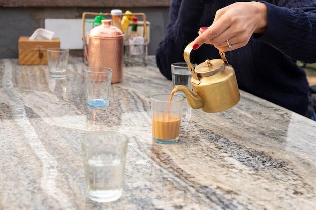 Tè di masala di versamento della donna dalla teiera nel cupglass sulla tavola in caffè.