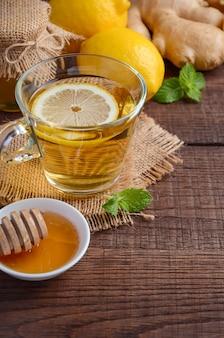 Tè di radice di zenzero con limone e miele sul tavolo di legno.