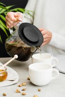 Tè di versamento della donna in tazza dal produttore di tè