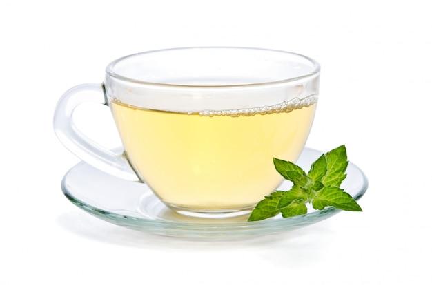 Tè di vetro della tazza con la menta, isolata su bianco.