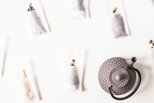 Tè diversi in sacchetti filtranti usa e getta per la preparazione accanto a un bollitore di ghisa grigia