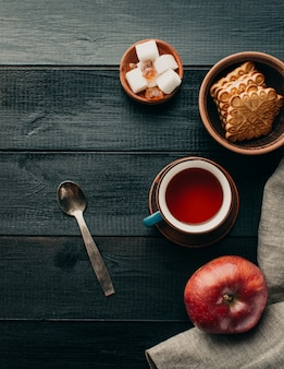 Tè e biscotti su una tavola di legno nera