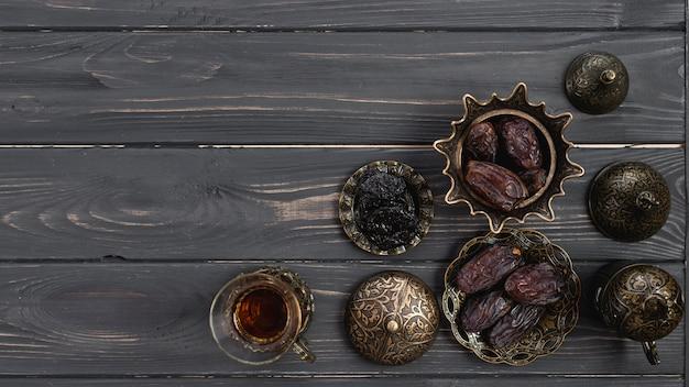 Tè e datteri tradizionali freschi sulla ciotola metallica sopra lo scrittorio di legno