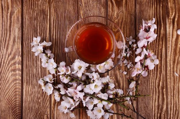 Tè e un ramo di fiori di ciliegio su un legno