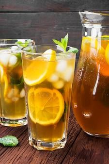 Tè freddo con limone e menta su un fondo di legno